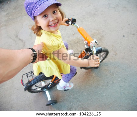 Little funny girl learning to ride a bike - stock photo