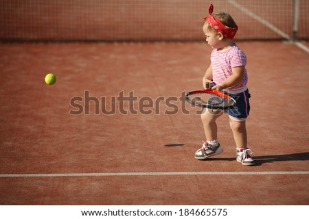 little funny girl plays tennis - stock photo