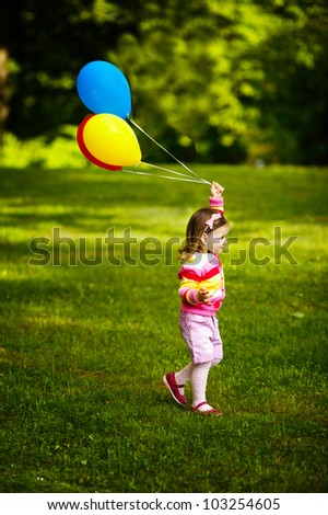 little funny girl plays with balloons in park - stock photo