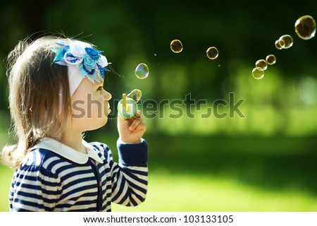 little funny girl plays with bubbles - stock photo