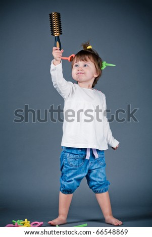 little funny girl plays with comb - stock photo