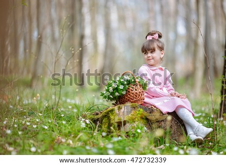 Little funny girl rests on the stump in forest