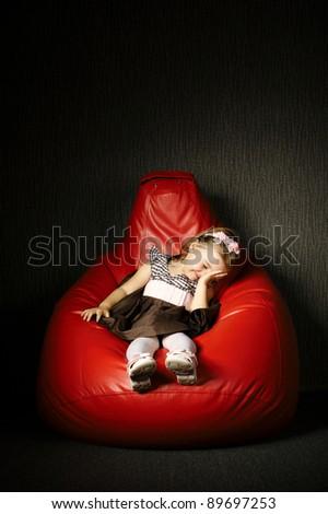 Little funny girl sitting on red beanbag - stock photo