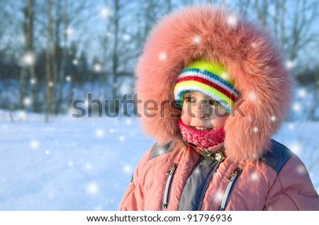 Little funny girl walking a winter sunny day. - stock photo