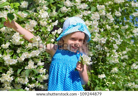 Little funny girl with blooming jasmine bush. - stock photo