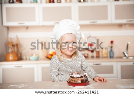 Little funny girl with chef hat and mouth full of cake. Kitchen interior. Concept for young kitchen hands