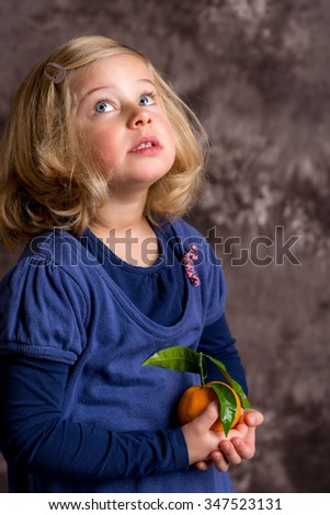 little funny girl with mandarin orange in front of brown background - stock photo