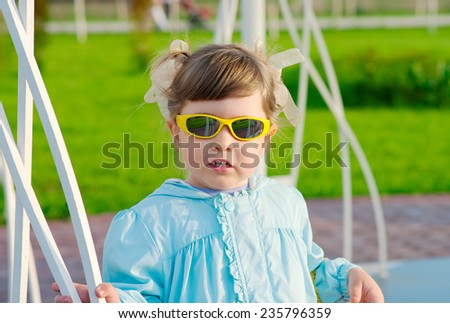 Little funny girl with sunglasses - stock photo
