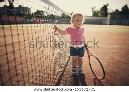 little funny girl with tennis racket - stock photo