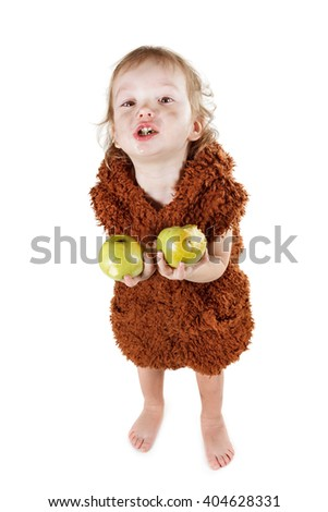 Little funny Neanderthal boy in a suit with a dirty face eating an apple. Humorous concept ancient caveman. Isolated on white. - stock photo