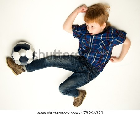 Little funny redhead boy kicking soccer ball - stock photo