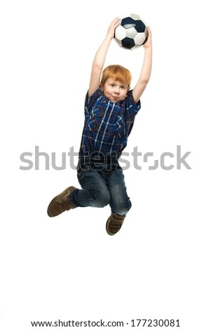 Little funny redhead boy with soccer ball jumping  - stock photo