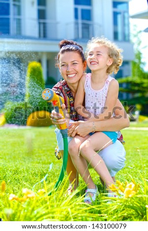 Little gardener girl with mother watering flowers on the lawn near cottage. Vertical view - stock photo