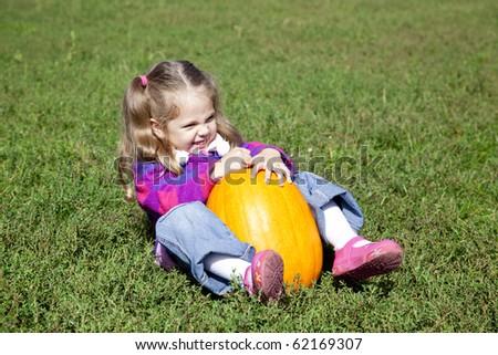 Little gardener girl with pumpkin at green grass - stock photo