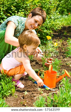 Little gardener helping mom - stock photo