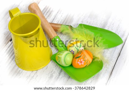 little gardening tools and easter eggs on white wooden table  - stock photo