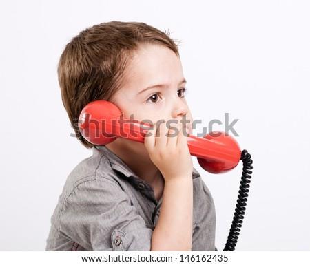 Little gay boy talking on a retro telephone. - stock photo