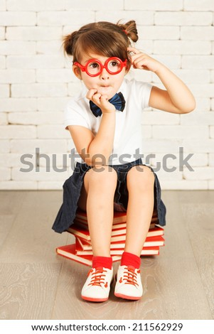 Little genius girl in glasses sitting on a books. - stock photo
