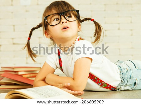 Little genius in glasses with books