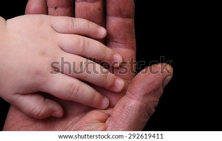 Little gentle hand of the child in the rough hand of the worker