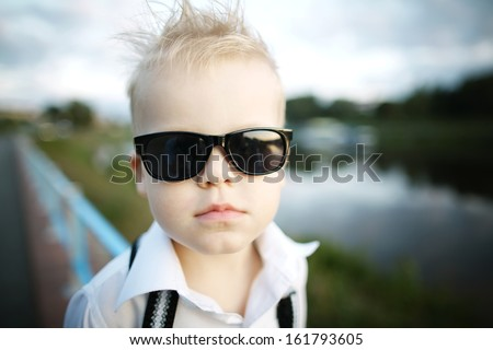 little gentleman with sunglasses outdoors - stock photo