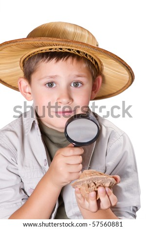 Little geologist examining desert rose crystal with magnifying glass - stock photo
