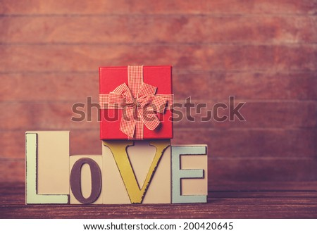 Little gift and word Love on wooden table. - stock photo