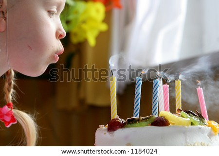 Little gilr blowing birthday candles - stock photo