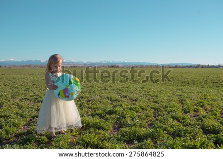 Little gilr 3-4 standing in large hay field playing with a globe ball. - stock photo
