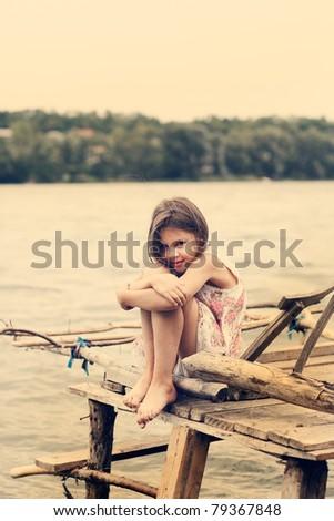 Little girl a park near the river - stock photo