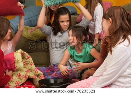 Little girl about to get whacked with a pillow at a sleepover - stock photo