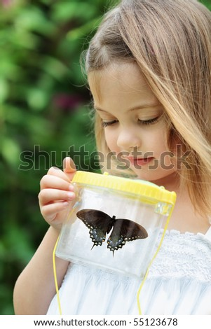 Little girl admires a Spicebush Swallowtail butterfly that she has captured. - stock photo