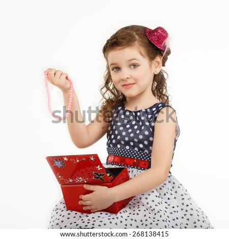 little girl admires the accessories in the box isolated on white background - stock photo