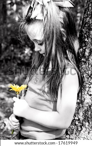 Little girl admiring her yellow flower while leaning against a tree. - stock photo