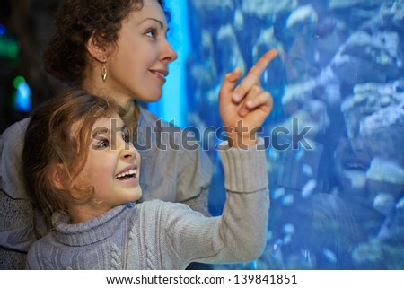 Little girl admiringly shows her mother something in big aquarium at oceanarium, focus on girl face - stock photo