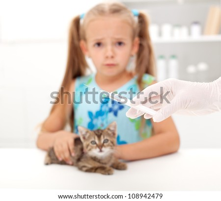Little girl afraid for her kitten getting a vaccine at the veterinary - focus on syringe - stock photo