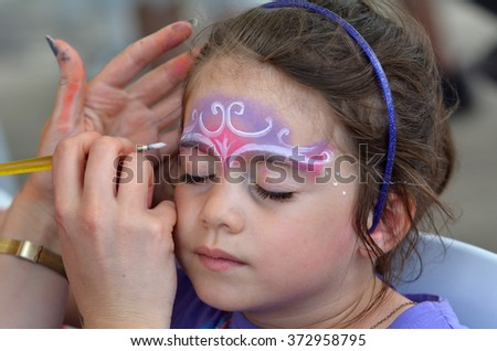 little girl (age 5-6) getting her face painted with a crown like a princes by face painting artist. - stock photo