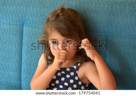 Little girl (age 3-4) sucks thumb at home. Concept photo of healthcare and early childhood - stock photo