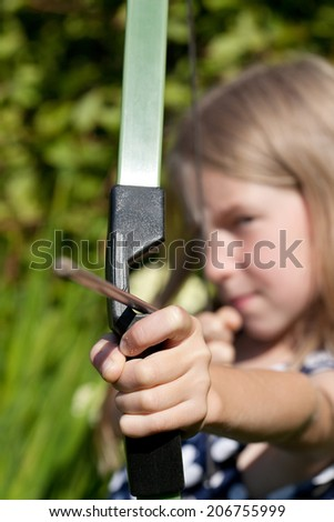 little girl aiming arrow from big bow, focus on hand - stock photo