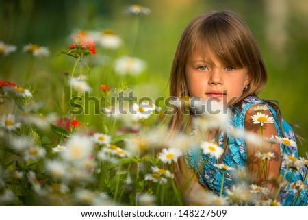 Little girl among wildflowers  - stock photo