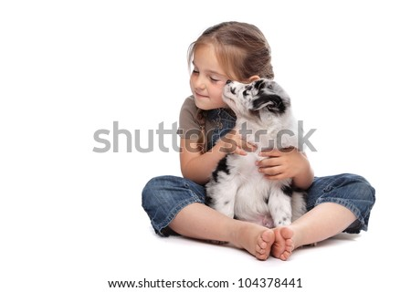 little girl and a puppy in front of a white background