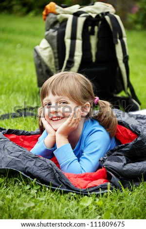 little girl and a sleeping bag - camping concept - stock photo