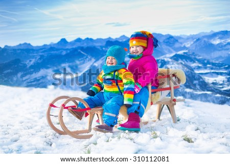 Little girl and baby boy enjoying a sleigh ride in the Alps mountains. Child sledding. Toddler kid riding a sledge. Children play outdoors in snow. Kids sled. Outdoor winter fun for Christmas vacation - stock photo