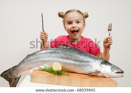 Little girl and big fresh fish - healthy eating seafood - stock photo