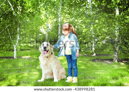 Little girl and big kind dog in the park