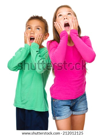 Little girl and boy are holding their faces in astonishment while looking up, isolated over white - stock photo