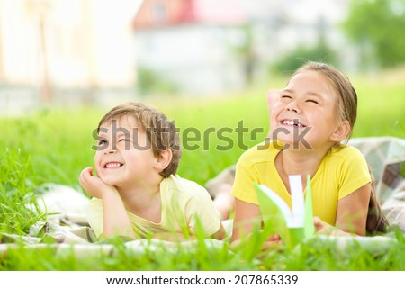 Little girl and boy are playing outdoors while laying on green grass - stock photo