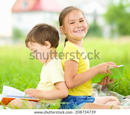 Little girl and boy are reading books while sitting on green grass - stock photo