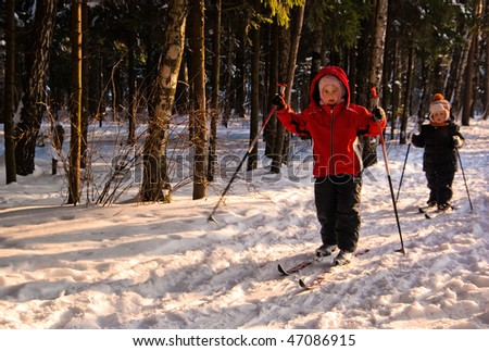 Little Girl and Boy Cross Country Skiing. Focus on girl in red - stock photo