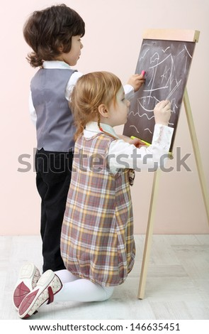 Little girl and boy draw by chalk ship in sea at chalkboard in studio. - stock photo